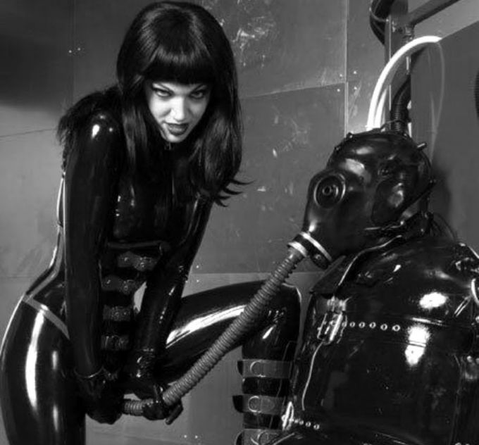 Mistress in latex and slave with gas mask