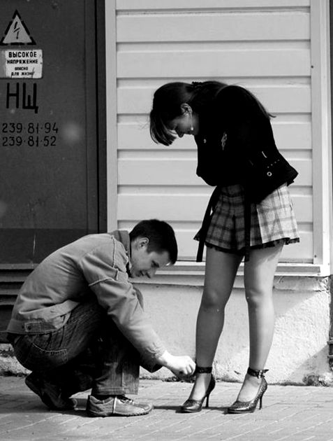 Man kneeling to fix woman's shoe