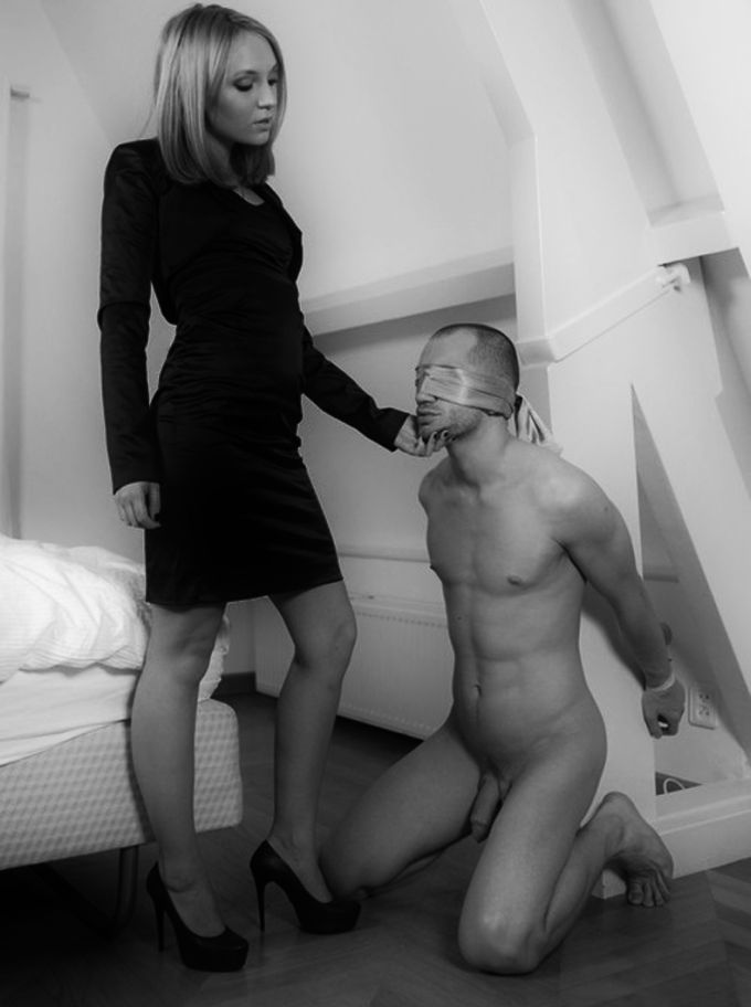 Lady in high heels with a naked bound man